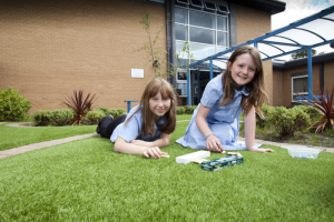 Children at Westfield School relaxing on the LazyLawn artificial grass