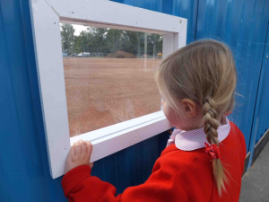 Little girl looking through a viewing panel